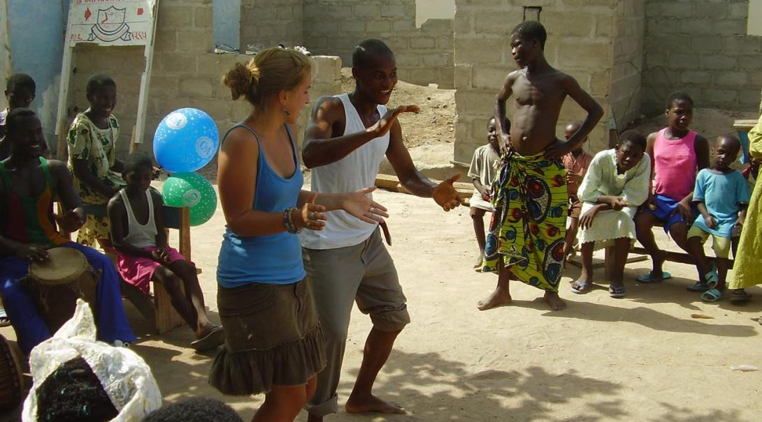 A Projects Abroad teaching volunteer dances with a local community in Ghana.